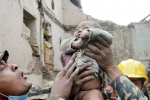 "In this Sunday, April 26, 2015, photo taken by Amul Thapa and provided by KathmanduToday.com, four-month-old baby boy Sonit Awal is held up by Nepalese Army soldiers after being rescued from the rubble of his house in Bhaktapur, Nepal, after Saturday's 7.8-magnitude earthquake shook the densely populated Kathmandu valley.  Thapa says that when he saw the baby alive after 20 hours of rescue efforts ""… all my sorrow went. Everyone was clapping. It gave me energy and made me smile in spite of lots of pain hidden inside me."" (Amul Thapa/KathmanduToday.com via AP)"